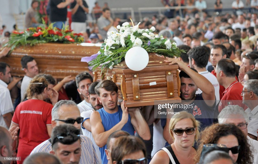 Friends and relatives of the victims of the Monteforte Irpino coach crash act as pallbearers during the funeral held at a local indoor sports arena on July 30, 2013 in Pozzuoli, Italy. In the second major European transport disaster in a week, 38 people were killed when a coach bus fell from a viaduct near Monteforte Irpino, Italy on July 28.