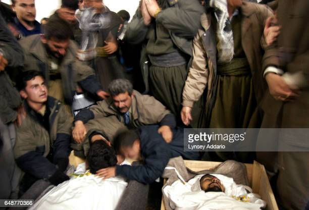 Friends and relatives stand over the bodies of some of five men killed in a shoot out at a PUK checkpoint in Suleimaniya Northern Iraq March 5 2003...