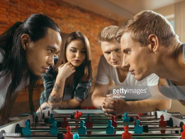 Amis se préparent à jouer le jeu de football/kicker de table