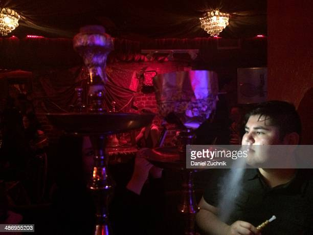 Friends are smoking hookah at Khyber Pass restaurant on St Marks Place in New York City