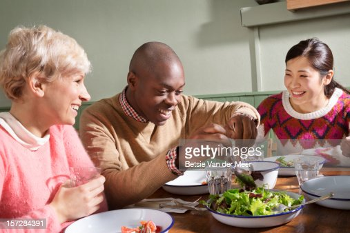 Friends around table laughing, serving food. : Stock Photo