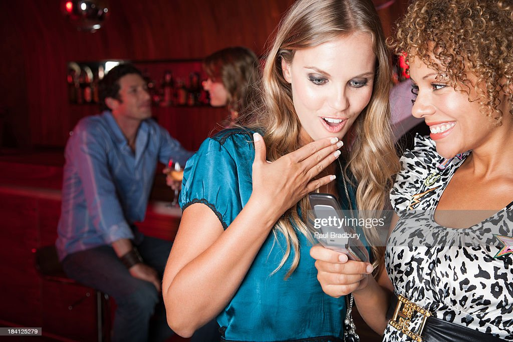 Friends at a club looking at a cellular phone : Stock Photo