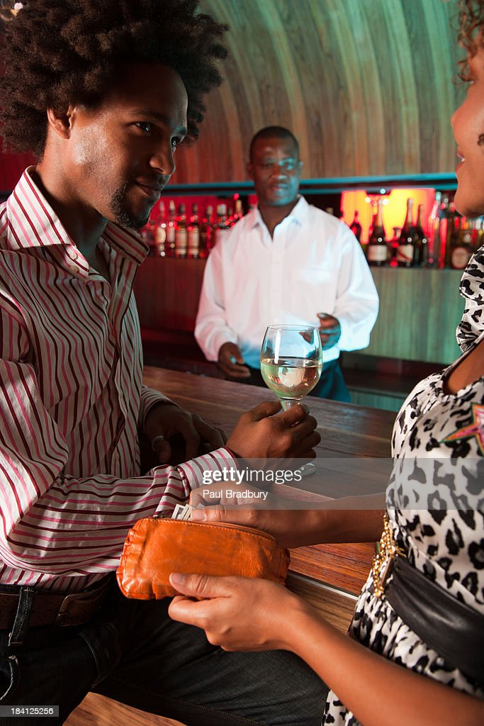 Friends at a club paying for something : Stock Photo