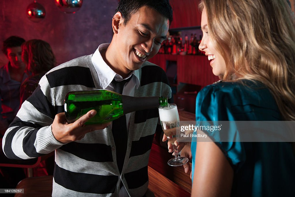 Friends at a club putting drinks : Stock Photo