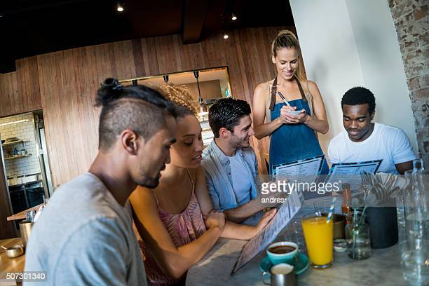 Friends at a coffee shop ordering to waitress