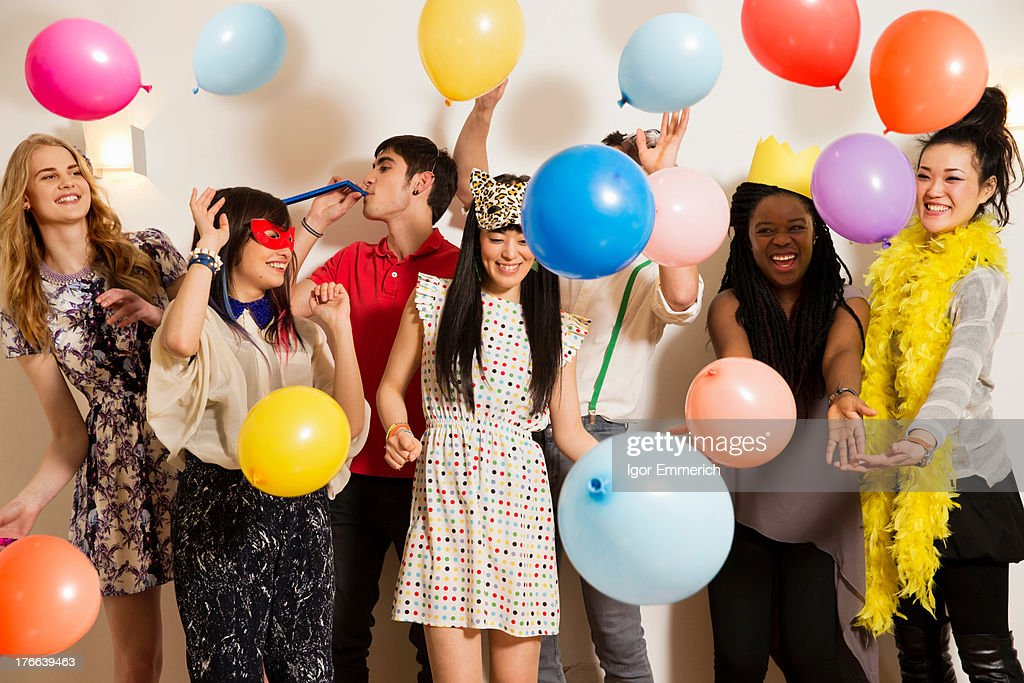 Friends at a party with balloons, studio shot : Stock Photo