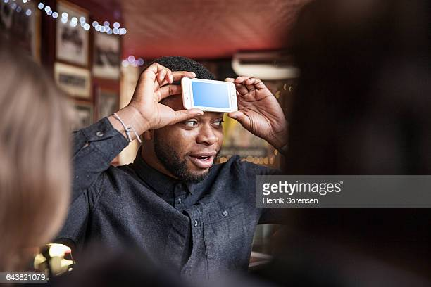 friends at a pub, young man with phone