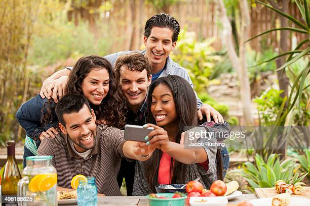 Friends at barbecue, taking self portrait photograph using smartphone
