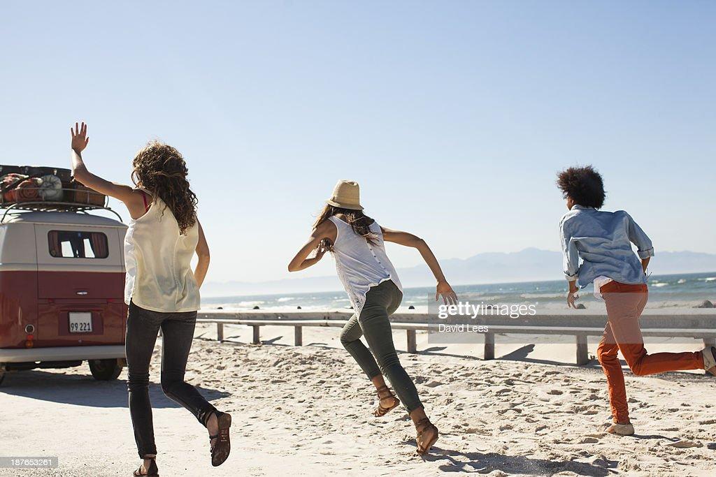 Friends at beach running after camper van