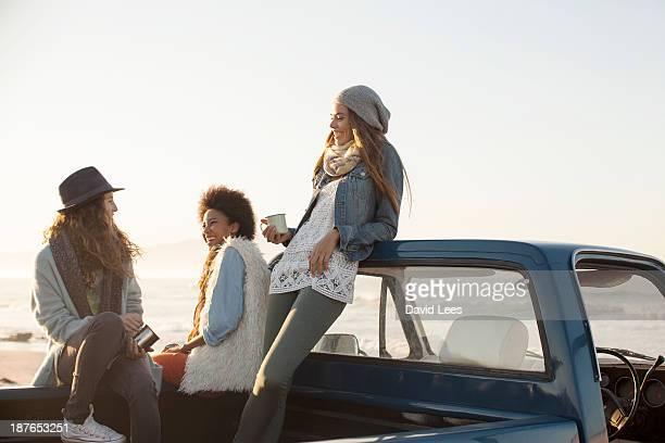 Friends at beach sitting in truck