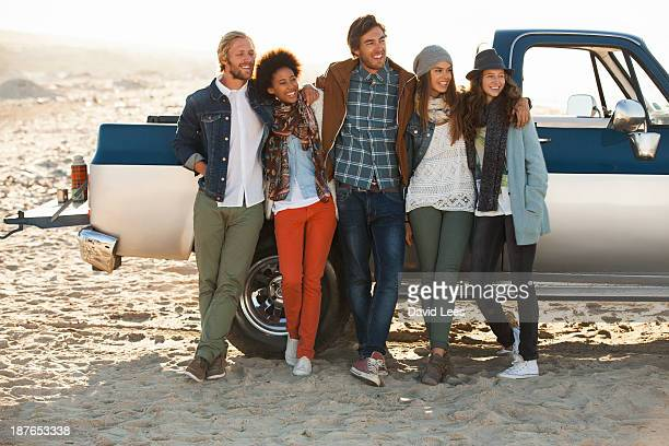 Friends at beach standing by truck