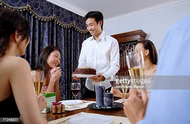 Friends at dining table, man giving cake to woman