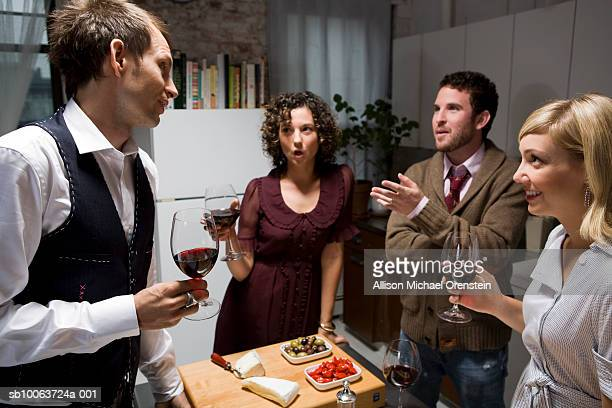 Friends at dinner party, holding wine glasses