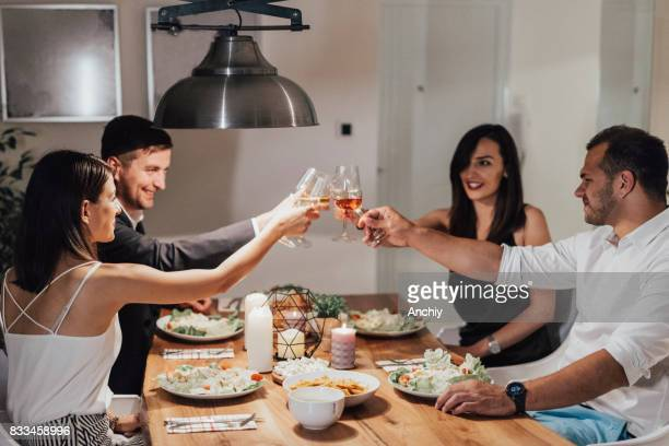 Friends at dinner party toasting with glasses
