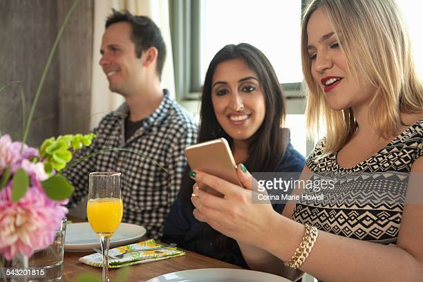Friends at dinner table, young woman showing friend smartphone screen