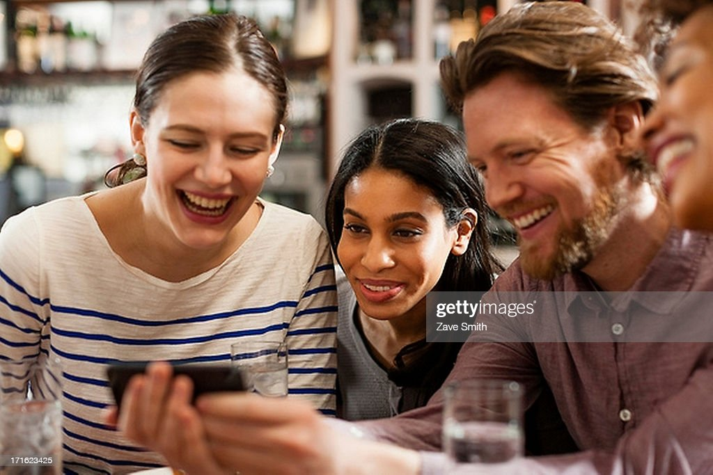 Friends at restaurant texting and showing photos using cell phones : Stock Photo