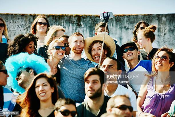 Friends at sporting event using a selfie stick