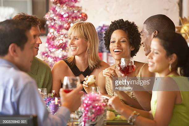Friends at table having christmas dinner, smiling