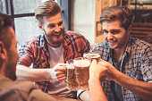 Handsome friends are clinking glasses of beer and smiling while resting at the pub