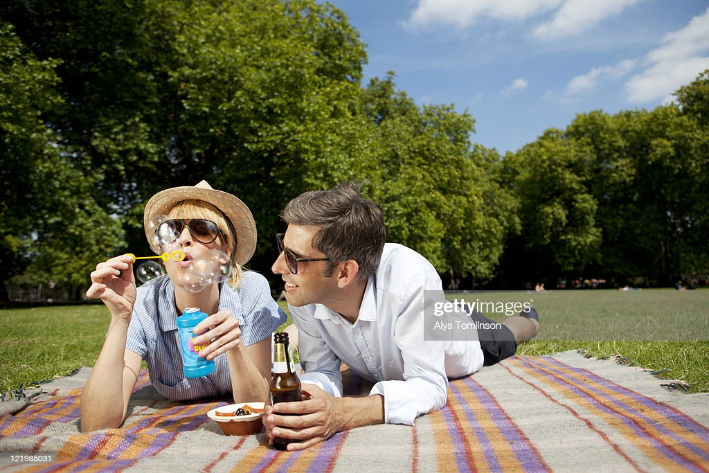 Friends Blowing Bubbles and Relaxing in a Ciy Park : Stock Photo