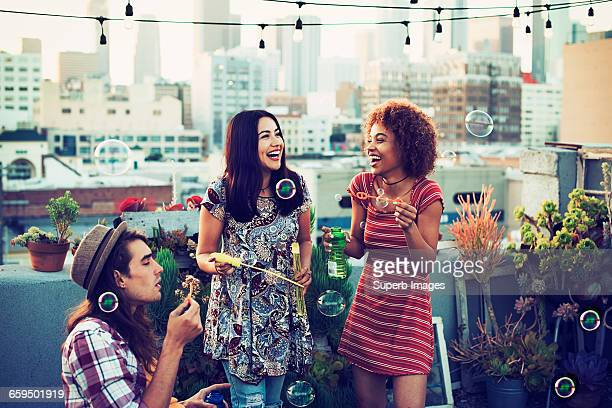Friends blowing bubbles on urban rooftop