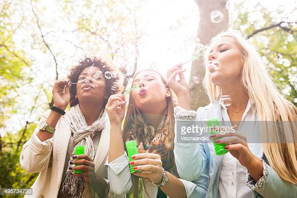 Friends blowing bubbles outdoors