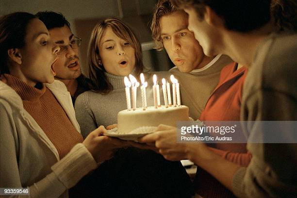 Friends blowing out birthday candles together