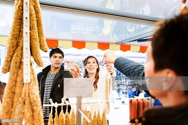 Friends buying sausages at store