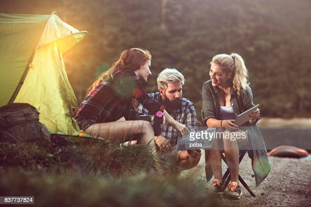 Friends camping beside river and planning a route on a map