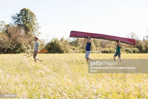 Friends carrying canoe in field
