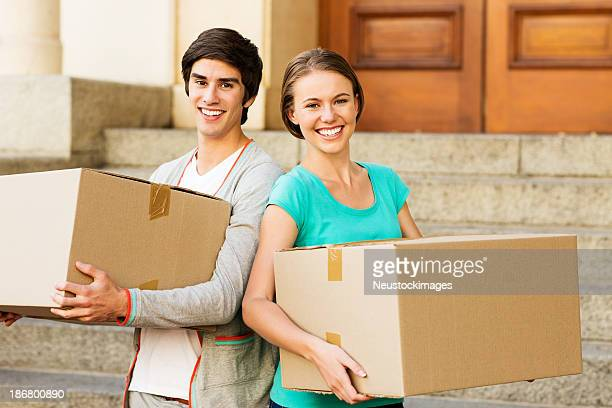 Friends Carrying Cardboard Boxes In Front Of New Dorm