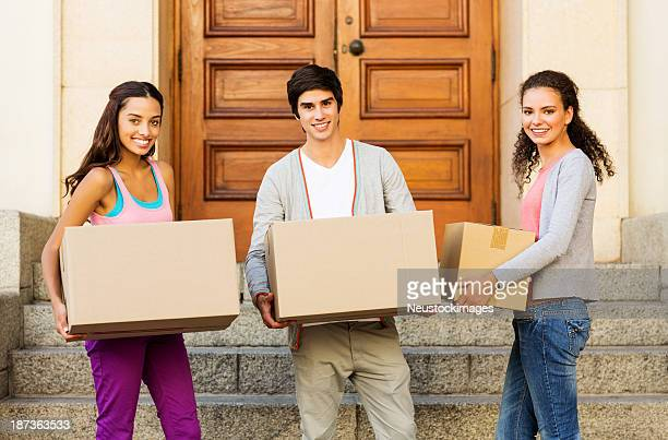 Friends Carrying Cardboard Boxes In Front On House