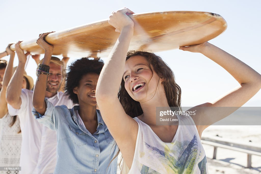 Friends carrying surfboard on heads : Stock Photo
