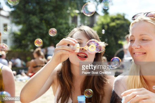 Friends catching bubbles with their plastic wand : Stock Photo