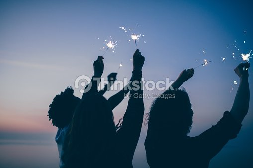 Friends celebrate party with sparklers and firework at sunset : Stock Photo