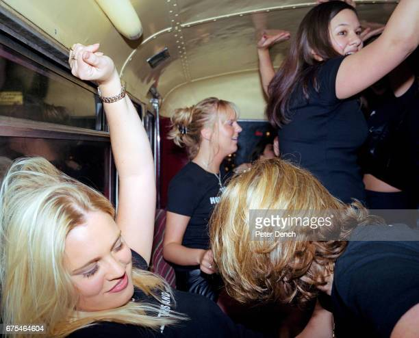 Friends celebrating a 21st birthday dance on a party bus as it travels down London's busy Oxford Street The bus stops at a number of nightclubs and...