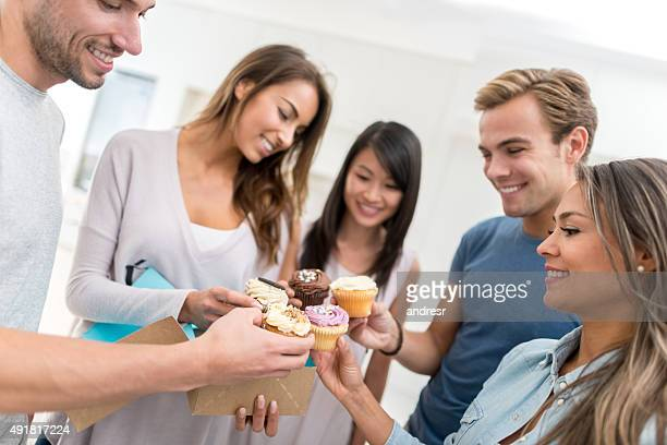 Friends celebrating a birthday and eating cupcakes
