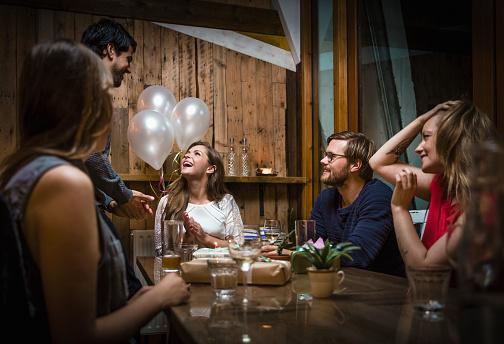 Friends celebrating birthday in restaurant