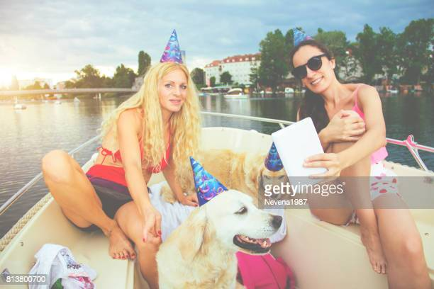 friends celebrating birthday on the boat with dogs
