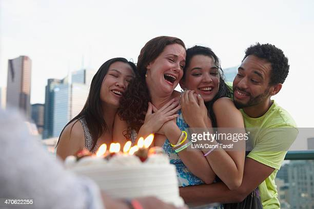 Friends celebrating birthday on urban rooftop