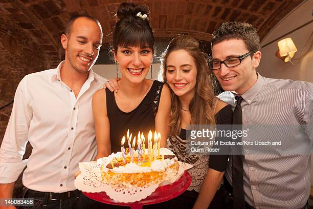 Friends celebrating birthday with cake