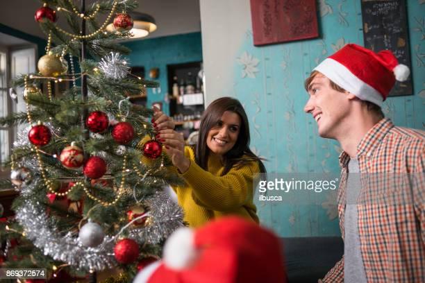 Friends celebrating Christmas: Preparing the Christmas tree