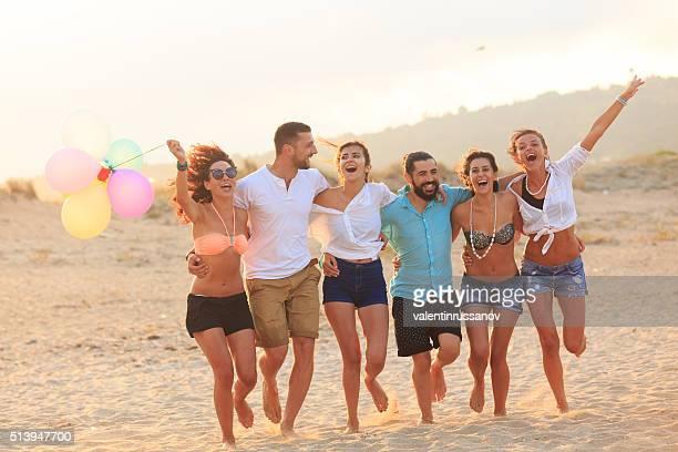 Friends celebrating on beach holding balloons