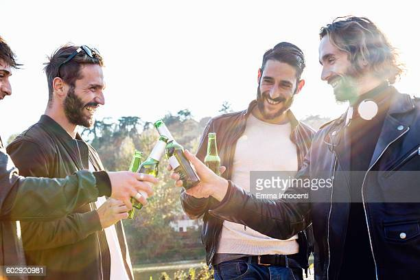Friends celebrating toasting beer on city holiday