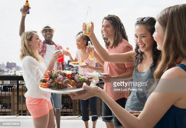 Friends cheering at barbecue outdoors