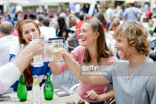 Friends cheering at outdoor cafe. : Stock Photo