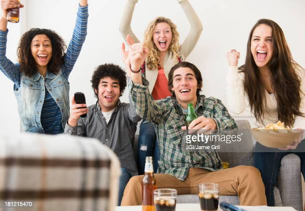 Friends cheering in living room