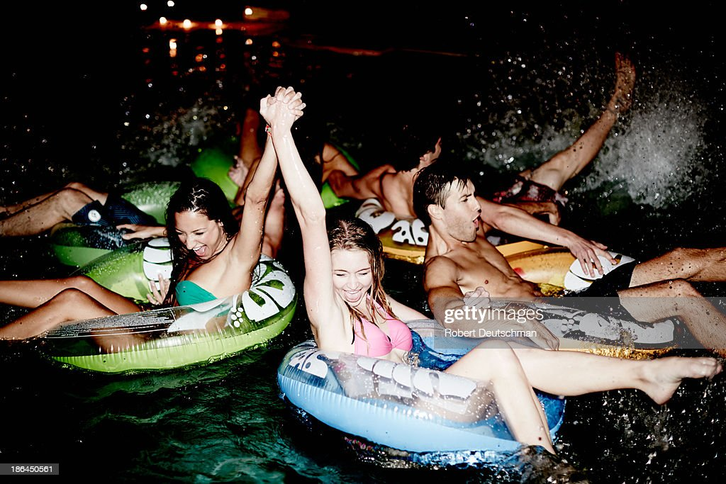 Friends cheering in the pool at night. : Stock Photo