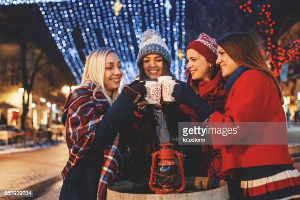 Freunde jubeln auf einer Straße mit Weihnachtsbeleuchtung geschmückt