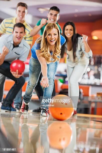 Amigos a celebrar enquanto Menina está a lançar uma Bola de bowling